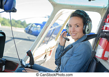 pretty pilot woman in helicopter ready to takeoff
