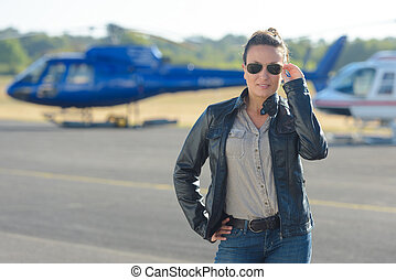 pretty pilot woman posing with helicopter in the background
