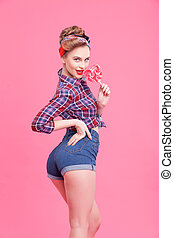 Pretty pin-up girl is playing with lollipop