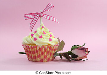 Pretty pink cupcake with pale pink silk rose bud on pink background for female birdthay, wedding, Valentine or Mothers Day.
