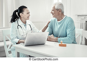 Pretty pleasant doctor talking to her patient and smiling. -...