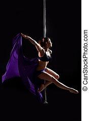 Pretty pole dance woman with purple fabric