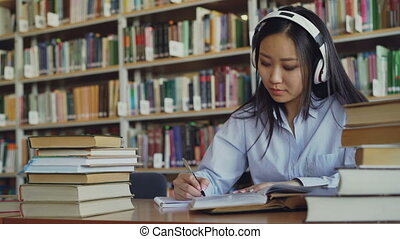 Pretty positive asian teenage student with headphones on...
