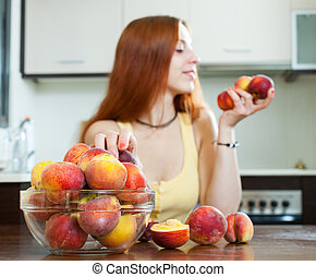 woman holding peaches in home kitchen. Focus on fruits