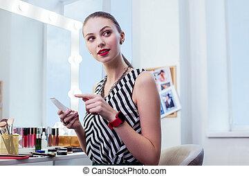Pretty positive woman using high quality cosmetics
