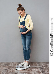 Pretty pregnant lady standing on scales