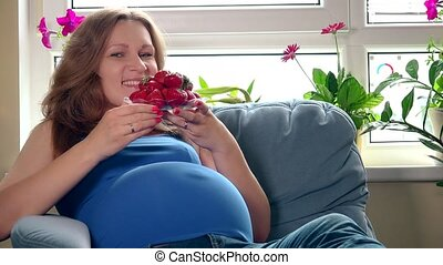 Pretty pregnant woman eating strawberries and smiling looking at camera