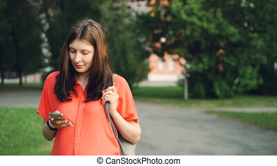 Pretty pregnant woman is using smartphone looking at screen walking in park on summer day. Modern technology, healthy lifestyle and pregnancy concept.