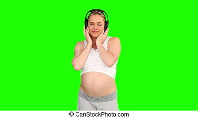 Pretty pregnant woman listening to music with a headphones