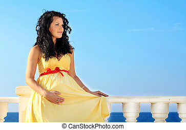 Pretty pregnant woman over sky in yellow dress