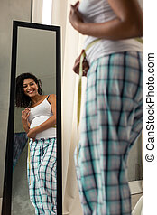 Pretty pregnant woman smiling at the mirror.