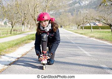 pretty preteen girl on roller skates in helmet