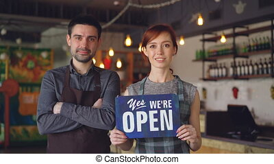 """Pretty red-haired businesswoman cafe owner is holding """"yes we are open"""" sign with her employee in apron standing near her. Successful start-up and people concept."""