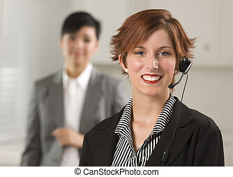 Pretty Red Haired Businesswoman and Colleague with Headset in Office Setting.