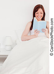 Pretty red-haired female reading a book while sitting on her bed