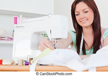 Pretty red-haired female sewing in the living room