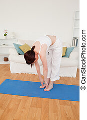 Pretty red-haired female stretching in the living room
