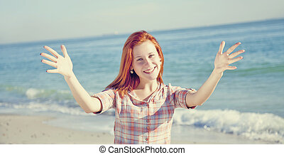 Pretty red-haired girl at the beach.