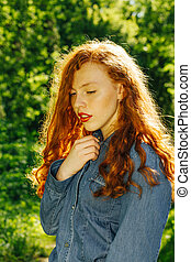 Pretty red haired model in blue jeans shirt in rays of sun at the park