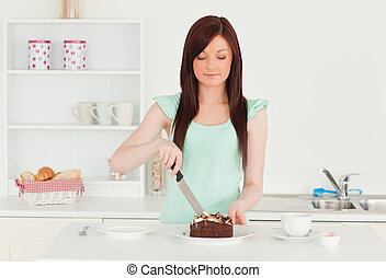 Pretty red-haired woman cutting some cake in the kitchen