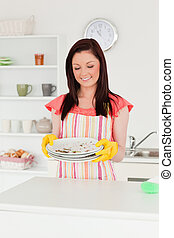 Pretty red-haired woman holding some dirty plates in the kitchen in her apartment