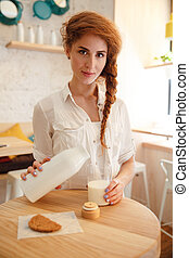 Pretty red haired woman pouring milk in glass from bottle
