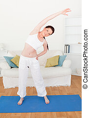Pretty red-haired woman stretching in the living room in her...