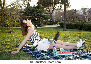 pretty red haired woman working on laptop in a park
