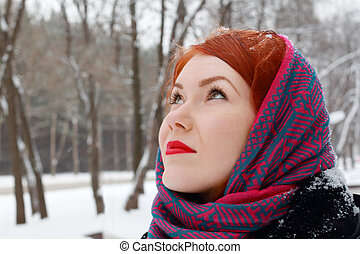 Pretty redhead girl in red kerchief looks up outdoor at winter