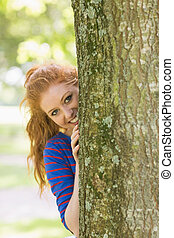 Pretty redhead hiding behind a tree