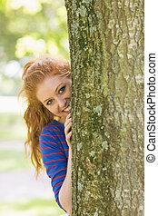 Pretty redhead hiding behind a tree