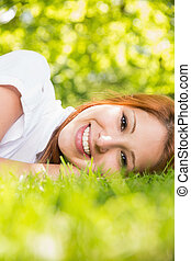 Pretty redhead smiling at camera lying on the grass