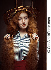 Pretty redhead woman with long curly hair in straw hat posing near the old door