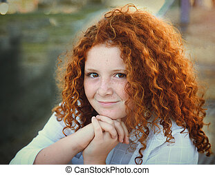 redhead young girl with curly hair portrait outdoors