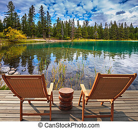 Two comfortable lounge chairs - Pretty round lake in the...