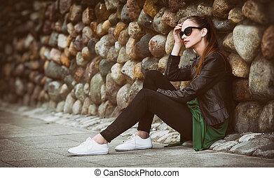 pretty sad girl sits on street.