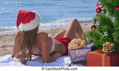Pretty Santa with gift boxes under Christmas tree on a sandy beach enjoying vacation