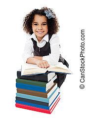 Pretty schoolgirl reading a textbook