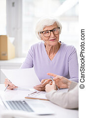 Pretty senior woman in eyeglasses and casualwear holding insurance document