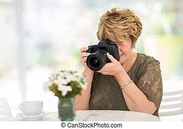 pretty senior woman photographing flowers on the table