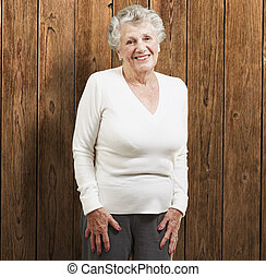 pretty senior woman smiling against a wooden background