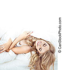 Pretty, sensual blonde relaxing in the bright bedroom