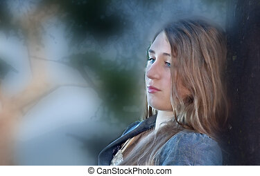 This is a pretty Caucasian 17 year old girl portrait. She is outdoors leaning against a tree with the background blurred. She has long, light brown hair and blue eyes, and has a thoughtful expression.