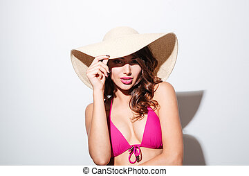 Pretty sexy beach girl wearing hat looking at camera
