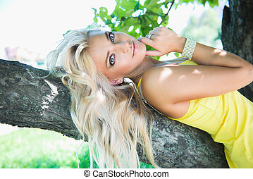 Pretty sexy blonde woman lying on tree bench