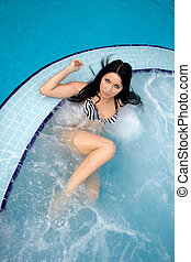 Pretty sexy brunette swimming in a pool