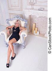 Pretty sexy brunette woman sitting on armchair