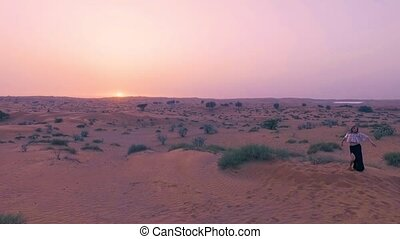 Pretty sexy girl dances in desert with sun on background....