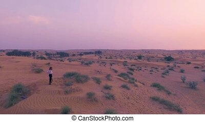 Pretty sexy girl dances in desert with sun on background. Happy beautiful woman is dancing east dance on sand at sunset. Drone aerial shot. Slow motion