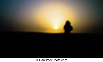 Pretty sexy girl dances in desert with sun on background. Happy beautiful woman is dancing east dance at sunset. Dancer melts, dissolves in sunset. Slow motion